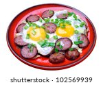 Fried eggs with sausage and green onions in a red plate isolated on white background - stock photo