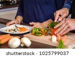 young couple cutting vegetables ... | Shutterstock . vector #1025799037