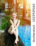 Small photo of young woman relax near swimming pool, enjoy weather in tropical country on background of apartment building on sunny day with sunshine. Concept of enjoying life, tratement for healthy body and