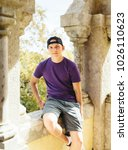 Small photo of Young handsome man wearing purple t-shirt and cap is looking forward and sitting on ancient castle wall. Portrait of modern guy. Portugal, The Pena Palace.