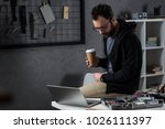 man with coffee in hand sitting ...   Shutterstock . vector #1026111397