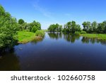 landscape with calm river water and green trees in sunny day - stock photo