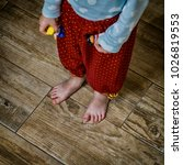 Small photo of Little bare baby feet stand on the wooden tile floor