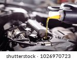 motor oil pouring to car engine. | Shutterstock . vector #1026970723