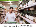Young man looking at bottle of wine in supermarket - stock photo