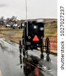 Small photo of Abstract of Amish Buggy Driving through the Rain on Edge of Wet Road with Farmland in the Background; Raindrops Blurring Foreground