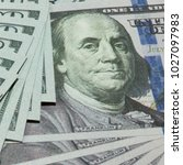 Small photo of close-up image of an American president on a 100 dollar bill and cache spread out as a background