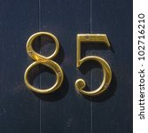 house number eighty-five in gold lettering on a background of dark blue lacquered wood - stock photo