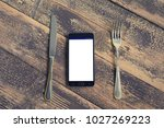 Small photo of Mobile phone on the menu, with fork and knife. Order online concept. Top view with copy space for text. Blogging concept.