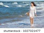 woman enjoying a walk on the... | Shutterstock . vector #1027321477
