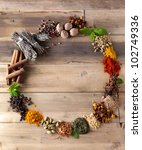 Beautiful circle of colorful spices and herbs on a wooden table - stock photo