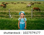 Small photo of Tilt shift blurred mood portrait of little girl. Young girl in blue dress relax in front of horse pasture outdoor at nature. Babe expressive emotional face. Childhood in village. Kid on school break