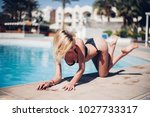 woman lying by the pool in a... | Shutterstock . vector #1027733317