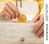 Small photo of Woman holding a bitcoin picking out her purse. Virtual cryptocurrency concept. Easy pay concept. Easy Online shopping, woman happy