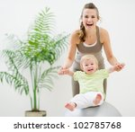 Mother and baby playing with fitness ball - stock photo