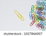 Small photo of Business concept for group of stacked paperclip with another one individual unique yellow paperclip standing along as a team leadership