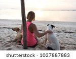 Stock photo young woman or girl caressing two dogs wearing sport clothing enjoying her time and vaction 1027887883