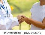 doctor holding elderly patient... | Shutterstock . vector #1027892143