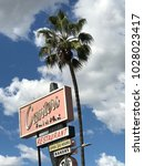 Small photo of LOS ANGELES,FEB 13th 2018: Close up of the famous sign above Canter's Restaurant and Deli on Fairfax Avenue in the Fairfax District of Los Angeles, against a blue sky with white clouds and palms.