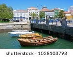 Small photo of PORTIMAO, PORTUGAL - JUNE 7, 2017 - Small boats moored against a bridge on the Arade River with city buildings to the rear, Portimao, Algarve, Portugal, Europe, June 7, 2017.