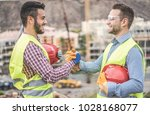 Small photo of Builders on residential construction site making a deal - Happy workers are satisfied of their plan - Dealing, real estate, engineer, industrial and building houses concept - Focus on hands