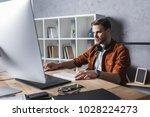 handsome young designer wrking... | Shutterstock . vector #1028224273