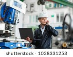 young engineer with laptop in... | Shutterstock . vector #1028331253