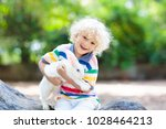 child playing with white rabbit.... | Shutterstock . vector #1028464213