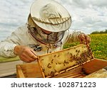 Working apiarist in a spring season. - stock photo