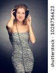young cheerful girl listening... | Shutterstock . vector #1028756623