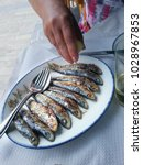 Small photo of a woman wring a lemon on a delicious sardine on a white plate