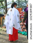 Stock photo a japan shinto shrine maiden prays and holds the ritual kuyo otakiage ceremony a grand bonfire 1029289387