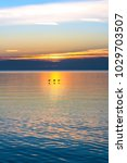 Small photo of Three birds flying low over tranquil waters aglow with blue, orange and yellow colors of sunrise. Tranquil, peaceful, relaxing nature scene