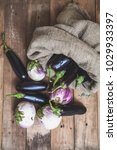 Small photo of canvas bag with blue eggplants lies on the planed boards. Nearby lie light lilac eggplant bumbo