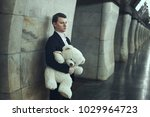Small photo of Sad Man holds a toy in the hands of a bear.