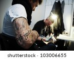 WARSAW - NOV 12: Tattooist makes a tattoo on his client's leg during the tattoo, body painting and pierceing show 'Body Art Convention' on 12th November, 2011 in Warsaw - stock photo