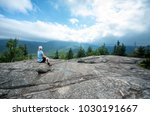 woman sitting on a rock at the... | Shutterstock . vector #1030191667