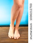 Small photo of young girl steppe feet with itchy feet uses his big toe to scratch his other foot on wooden floor