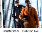 security guard leading prisoner ... | Shutterstock . vector #1030254163