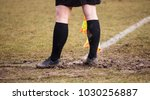 Small photo of Football soccer arbiter assistant stands at corner side with shoes full of mud and flag at hands. Blur green field background, close up.