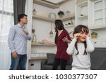 Small photo of The concept of parental family quarrels, Young Couple Parents are fighting in front of children. The children are very sad to the parents quarrel. Children are crying and headaches.