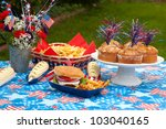 Cornbread, corn and burgers on 4th of July picnic in patriotic theme - stock photo