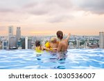 family swimming in roof top... | Shutterstock . vector #1030536007