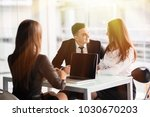 young couple sitting at a desk... | Shutterstock . vector #1030670203