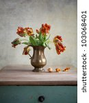 Ornamental orangey-yellow tulips in an antique metal jug with fallen petals on the old wooden tabletop - stock photo