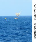 Small photo of Fishing boat with wellhead platform background.