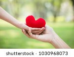 hand giving red heart to hand.... | Shutterstock . vector #1030968073