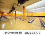 Empty bowling club, lot of bowling lanes with skittles, yellow walls and floor