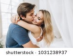 Small photo of Beautiful loving couple kissing and has fun in their bedroom near the window, a guy holding his beloved beautiful girl in his arms, motion blur