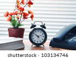 Office desk arrangement showing clock, phone, flower decoration and paperwork. Can be use to show work efficiency concept. - stock photo